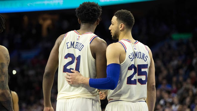 Philadelphia 76ers guard Ben Simmons (25) and center Joel Embiid (21) talk during a break in fourth quarter action against the Brooklyn Nets at Wells Fargo Center.