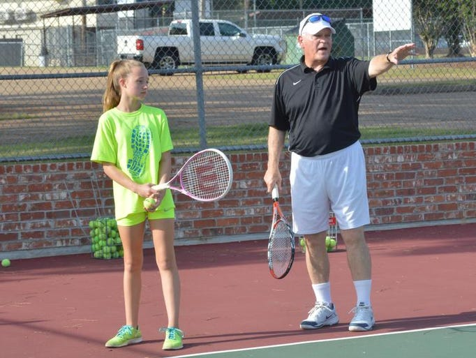 ANI Tennis USPTA tennis instructor Gary Childress (right) gives instruction to Kloe Franklin (left) who is one of the youngsters Childress is giving lessons to at the Ward 10 tennis complex Wednesday, July 16, 2014.