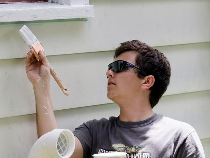 Eric Burgard, 17, of Sheboygan Falls paints trim on a North Side Sheboygan home Monday June 17, 2014 in Sheboygan during the 5th annual At Home Mission Week.
