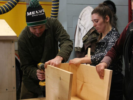 Mac Lynch of Winooski, left, and Jess Edwards of Williston help build a free library shelf at the Winooski Fire Department as part of the Onion City's MLK Day of Service on Monday, Jan. 15, 2018.