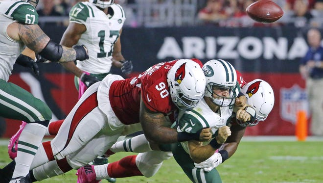Jets quarterback Ryan Fitzpatrick (14) loses the ball as he is brought down by Cardinals defensive tackle Robert Nkemdiche (90) and defensive end Calais Campbell (93) during the second quarter, Monday, Oct. 17, 2016 in Glendale, Ariz.