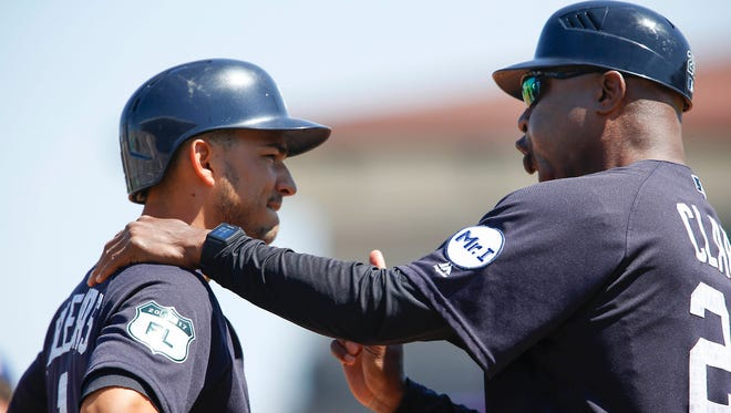 Tigers third base coach Dave Clark (25) talks to shortstop Jose Iglesias (1) who is on third base during the first inning of the Tigers' 5-1 exhibition win over the Mets Monday in Lakeland, Fla.