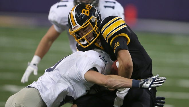 Bettendorf quarterback Cyle Cox (right, in 2013 photo) has led his team to a 7-0 record this fall.
