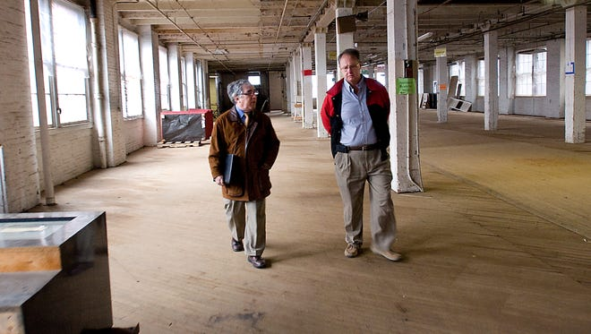 Larry Glazer, left, walks with Bob Kinsella of Volunteers of America in a former pasta factory  that Glazer bought from VOA in 2011.
