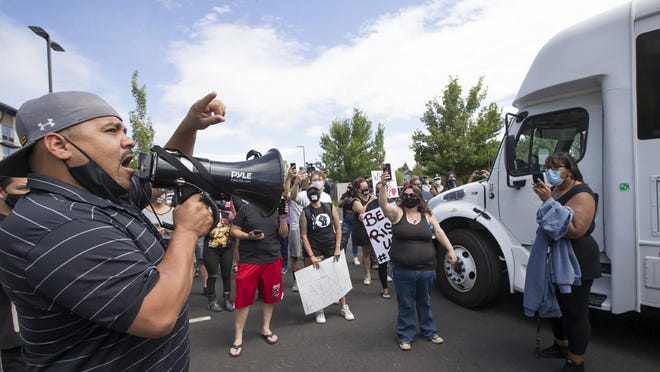 Gus Juarez tells the crowd the names of two men detained by federal immigration officials on Wednesday in Bend. Protesters surrounded two unmarked buses outside Crane Shed Commons to prevent officials from taking the men.