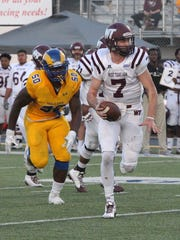West Texas A&M quarterback Justin Houghtaling (7) tries to elude Angelo State's Bright Ihegworo during a Lone Star Conference game at LeGrand Stadium at 1st Community Credit Union Field. ASU rolled to a 51-3 win on Saturday, Nov. 4, 2017. It was Senior Day for the Rams.