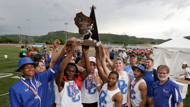 The Oak Creek boys track and field team hoists its trophy after taking second in the WIAA Division 1 meet on Saturday.