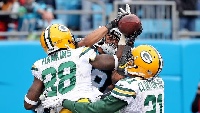 Green Bay Packers cornerback Josh Hawkins (28) and free safety Ha Ha Clinton-Dix (21) try to break up a pass to Carolina Panthers wide receiver Damiere Byrd (18) on Sunday, December 17, 2017 at Bank of America Stadium in Charlotte, N.C.
