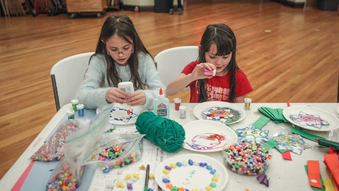 Jasmine, 9, and Destiny, 7, Bolin, of Lower Price Hill Girl Scout Troop 49632, make glittery snowflakes during their holiday party inside the Community Matters Sanctuary Wednesday December 16, 2015.