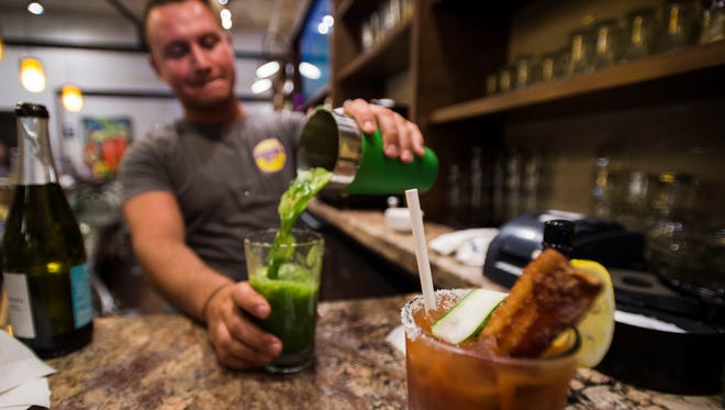 "Bartender Jeff Shrider makes a ""Green With Envy"" vegetable and fruit drink while a Bloody Mary sporting a paper compostable straw waits to be taken to a table on Thursday, June 28, 2018, at the Urban Egg, A Daytime Eatery in Fort Collins, Colo."