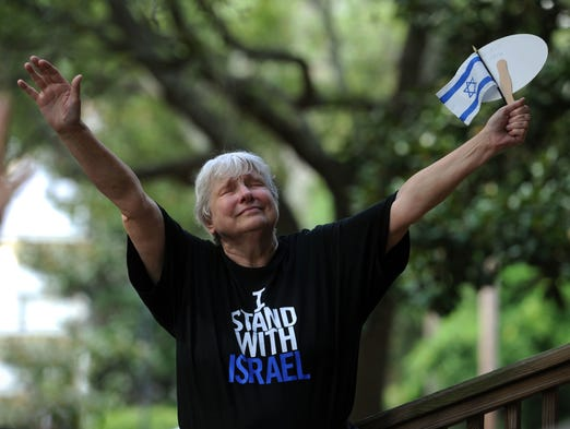 Linda Wolfe prays with the crowd for Israel Sunday during the Stand for Israel Rally at Seville Square.