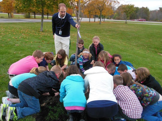 Principal Daniel Allen helps fourth-graders at Randolph Southern Elementary School in Lynn plant a tulip tree. This photo and the students' activities are featured in the December issue of the Indiana Bicentennial Commission's monthly communique.