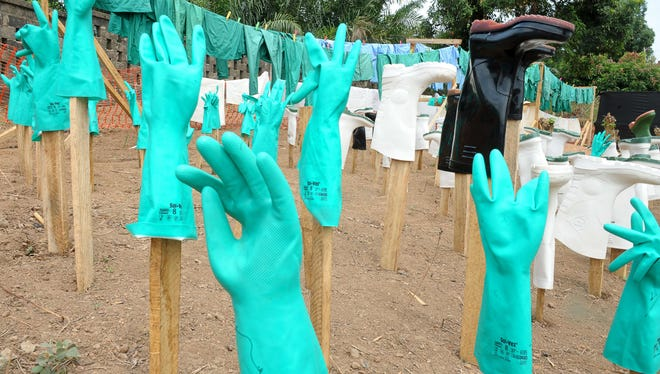 Gloves and boots used by medical staff dry in the sun at a center for victims of the Ebola virus in Guekedou. The epidemic in Guinea is caused by several viruses with similar symptoms. The deadliest and most feared of which is Ebola.