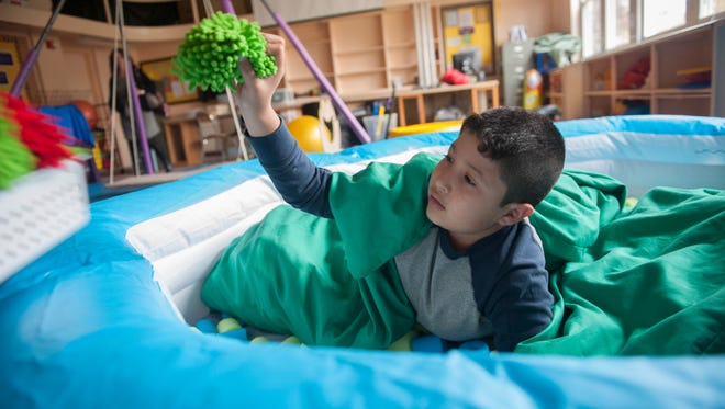 West End Elementary School fourth-grader Josue Guerrerro-Martinez plays during a session in the 'calming pit' in the sensory room for students with special needs at his Woodbury school.