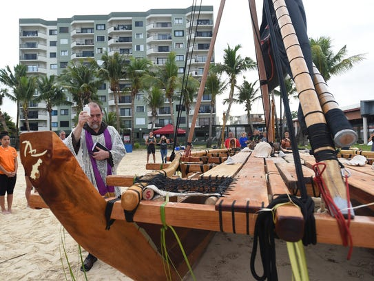 Father Eric Forbes blesses Ta Ina, Guam's first double-hull