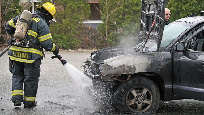 A Vineland firefighters puts out a car fire at a vacant gas station at Chestnut Avenue and Main Road Monday.