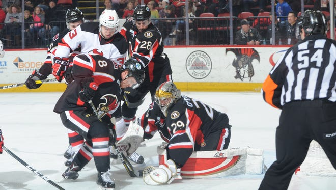 Binghamton Senators goalie Matt O'Connor covers the puck during Friday's American  Hockey League game against the Albany Devils at Floyd L. Maines Arena.