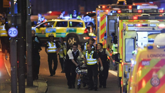 Police officers and members of the emergency services attend to a person injured in an apparent terror attack in central London.