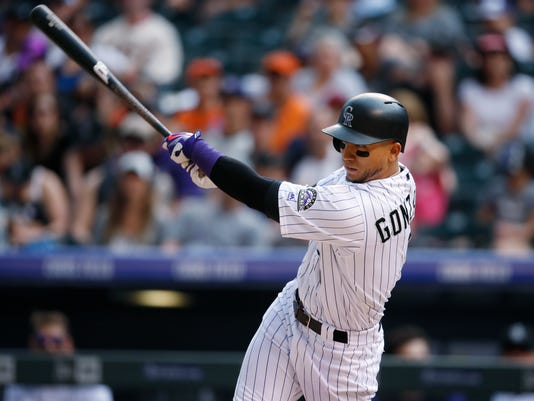 Colorado Rockies' Carlos Gonzalez follows through with his swing after connecting for a solo home run off San Francisco Giants relief pitcher Josh Osich in the eighth inning of a baseball game Sunday, May 29, 2016, in Denver. (AP Photo/David Zalubowski)