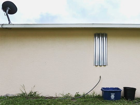 Every opening, to include the bathroom window, of Lula Florence's house is covered with hurricane shutters. Florence's uses the shutters to protect her family from shootings in the Dunbar community of Fort Myers.