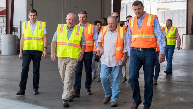 Harold McClarty, second from right, leads U.S. Secretary of Agriculture Sonny Perdue, second from left, and Representative David Valadao, right, Tuesday, August 14, 2018 on a brief tour of HMC Farms in Kingsburg. It was one of five planned stops for Perdue during a two-day pass through California. McClarty is the owner and hosted a discussion with local ag representatives after the tour.
