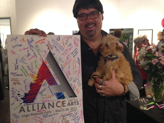 Byron McCartney of Brilliant Lens with Lucky and a congratulatory card featuring the new logo.