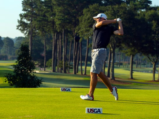In this photo released by the USGA, Corey Conners, of Canada, watches his tee shot on the first hole during the semifinal round of match play at the U.S. Amateur Championship golf tournament at Atlanta Athletic Club in Johns Creek, Ga., Saturday, Aug. 16, 2014.  (AP Photo/USGA, Chris Keane)