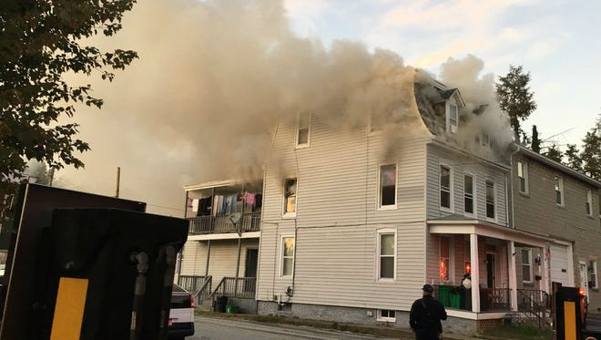 Smoke billows out of a home on Springdale Avenue Saturday. At least six people were displaced.