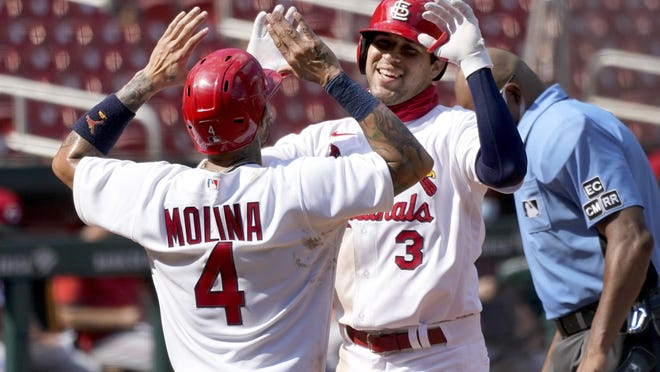 St. Louis Cardinals' Dylan Carlson, right, is congratulated by teammate Yadier Molina after hitting a two-run home run during the seventh inning of a baseball game against the Cincinnati Reds Sunday, Aug. 23, 2020, in St. Louis.