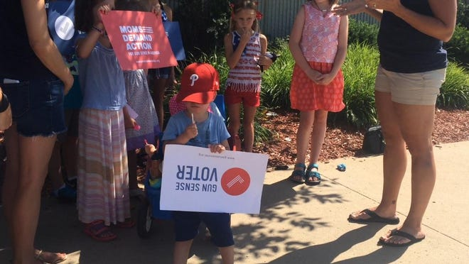 The activist group Moms Demand Action for Gun Sense in America met in front of an Ankeny movie theater Friday in response to a shooting at a theater in Lafayette, La.