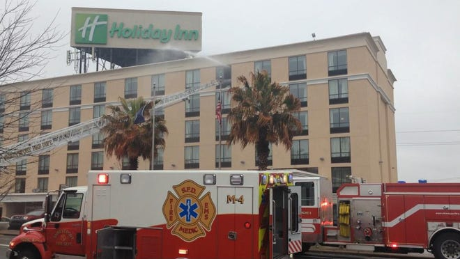 Water pours out a window Monday where about 20 units responded to a fire at the Holiday Inn.