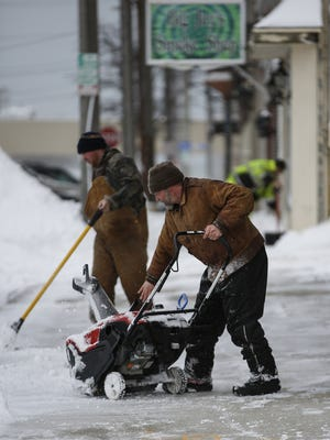 Brian Schwahert (right) and Matt Spevacek of Cretton Enterprises work to remove snow from the sidewalk at the corner of Ninth Street and Jay Street in Manitowoc as the snow returned to northeastern Wisconsin March 13.