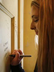 Senior McKenna Metzner takes part in the tradition of signing her name on the walls of Manitowoc Lincoln High School's tower Thursday. Some signatures on the wall date back as far as the 1950s.