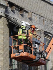 A crew rips down the metal cornice on the Village Square