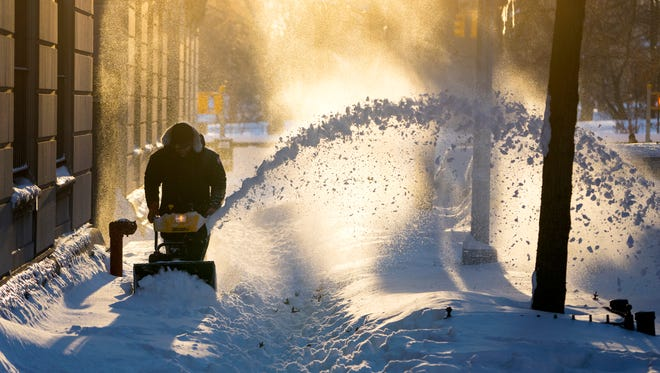 Snow is cleared along a street in the Upper West Side neighborhood of New York on Jan. 24, 2016, in the wake of a storm that dumped heavy snow along the East Coast.