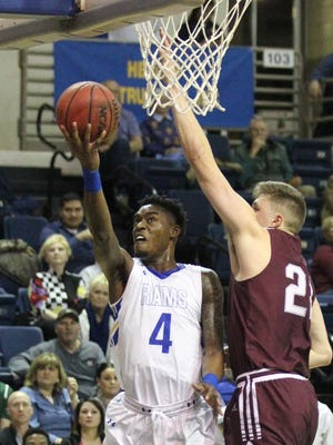 Angelo State University's Daron Mims (4) goes up for a layup against West Texas A&M's Ryan Quaid during a Lone Star Conference basketball game at the Junell Center on Thursday, Jan. 11, 2018.