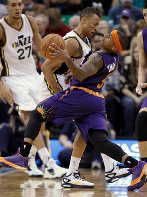 Utah Jazz' Dante Exum, left, cuts off and fouls Phoenix Suns Isaiah Thomas during the second half of an NBA basketball game in Salt Lake City, Saturday, Nov. 1, 2014. The Jazz defeated the Suns 118-91.