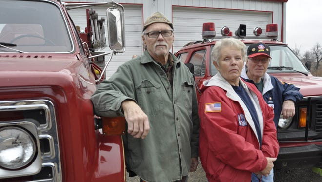 Membership President Jerry Price (left), Fire Chief Lucy Soltysik (center) and Assistant Chief Jerry Cousino stand between two of Oakland-Promise Land Volunteer Fire Department's oldest trucks, both more than 20 years old. Officials with the department say they want to form a fire protection district and charge residents a flat fee to improve fire protection for the service area.