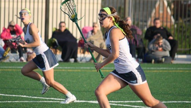 Mount Notre Dame freshman Julia Harmon, right, leads a break against McAuley on April 21.