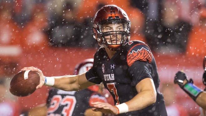 Utah quarterback Travis Wilson passes the ball during the first half .
