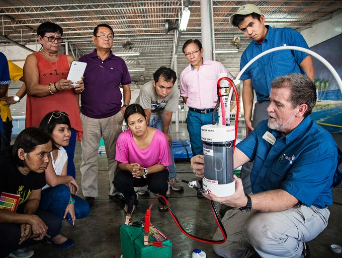 WaterStep held their first day of training at an old school in Cebu that is now a development center. Kurtis Daniels, front,  and Metropolitan Sewer District engineer Juan Afable, 23 were the main trainers of the kits chlorinator kits. They trained 50 people and gave out over a dozen chlorinator kits to help organizations set up the kits in various areas that were hit severely from the Typhoon. Kylene White/Special to the Courier-Journal