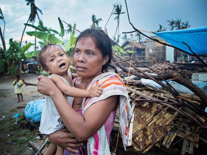 AnaLou Gilbuana, 33 with her son on Bontanyon Island which was hit hard by the Typhoon. She lost her entire house and is living under a tarp on the Island.  Kylene White/Special to the Courier-Journal