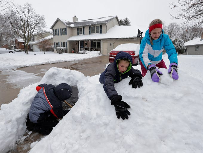 Bryce Rosenau, 13, left, makes a snow fort with his