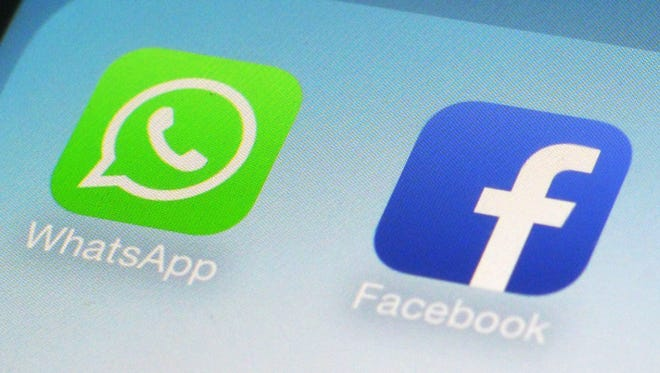 This Feb. 19, 2014, file photo, shows WhatsApp and Facebook app icons on a smartphone in New York. Global messaging service WhatsApp says it will start sharing the phone numbers of its users with Facebook, its parent company. That means WhatsApp users could soon start seeing more targeted ads on Facebook, although not on the messaging service itself.