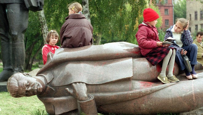 Moscow pupils take a break on a toppled statue of Stalin in a park in Moscow, Russia on Sept. 11, 1991.  (AP Photo/Dieter Endlicher)