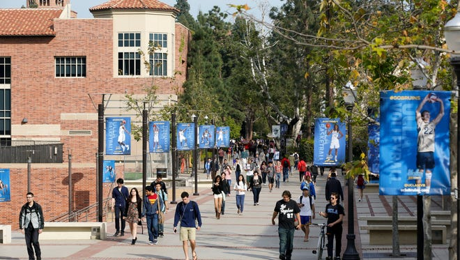 In this 2015 file photo, students walk on the UCLA campus in Los Angeles. The University of California says it has offered admission to nearly 70,000 California undergraduates, a slight dip from last year's historic high.