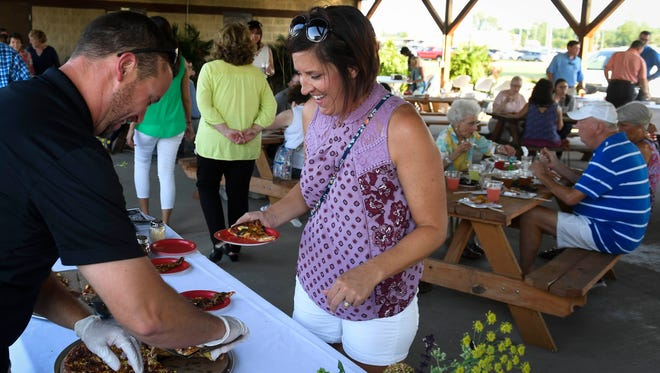 David Osborn with Rockhouse Pizza serves Tiffany Barrowclough at the Farm to Table event held at the Henderson County Fairgrounds Monday, July 10, 2017.