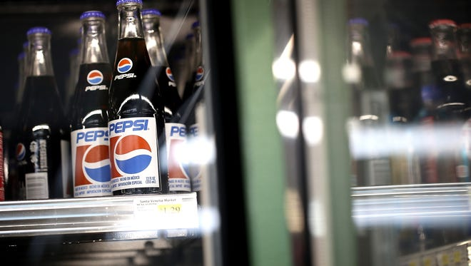 Bottles of Pepsi soda are displayed on a shelf.