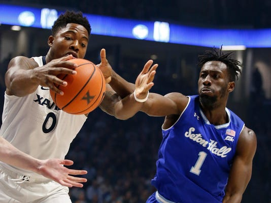 Xavier forward Tyrique Jones (0) and Seton Hall forward Michael Nzei (1) reach for a rebound during the second half of an NCAA college basketball game Wednesday Feb. 14, 2018, in Cincinnati. Xavier won 102-90. (AP Photo/Gary Landers)
