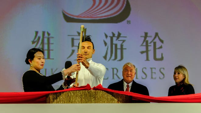 Yi Lou, vice president of China Merchants Bank Financial Leasing Co., Ltd., cuts a ribbon to trigger the smashing of a bottle of aquavit against the hull of Viking Sun.
